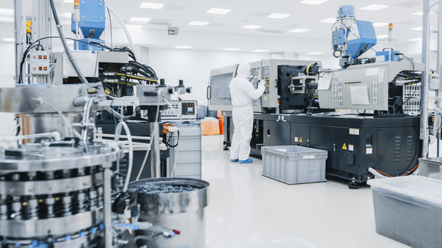 On a Factory Scientist in Sterile Protective Clothing Work on a Modern Industrial 3D Printing Machinery. Pharmaceutical, Biotechnological and Semiconductor Creating / Manufacturing Process