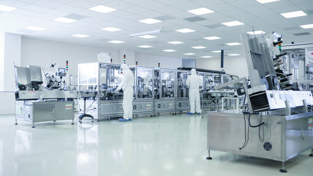 Sterile High Precision Manufacturing Laboratory where Scientists in Protective Coverall's Turn on Machninery, Use Computers and Microscopes, doing Pharmaceutics, Biotechnology and Research.