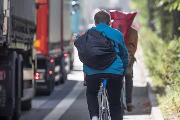 cyclists beneath trucks