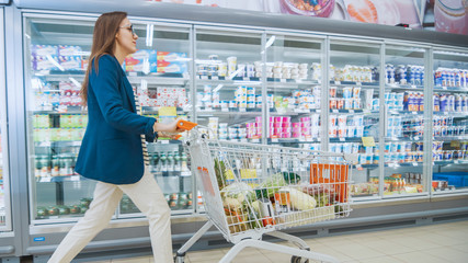 Beautiful Young Woman Pushes Shopping Cart full of Goods Through Frozen Goods and Dairy Section of the Supermarket.