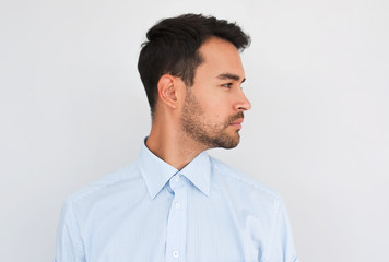 Profile view of handsome young handsome male wearing light blue shirt looking to the copy space for advertisement, posing on white studio background. People concept