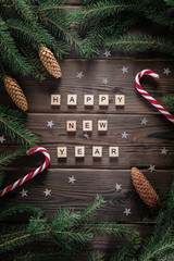 Happy new year phrase on woodden rustic table surounded with fur tree branches, cones, stars and candy canes.