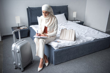 high angle view of young muslim woman sitting on bed and writing in notebook