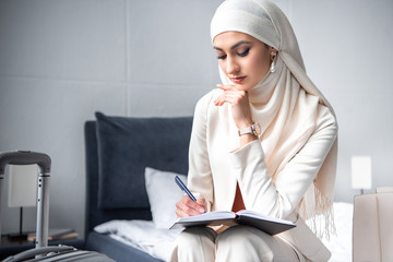 thoughtful muslim woman sitting on bed and writing in notebook