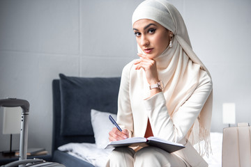 young muslim woman sitting on bed and looking at camera while writing in notebook
