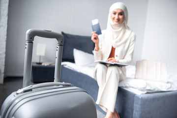 close-up view of suitcase and smiling muslim woman holding passport with boarding pass at home