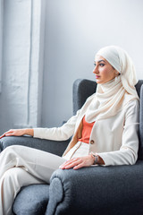 young muslim woman sitting in chair and looking away