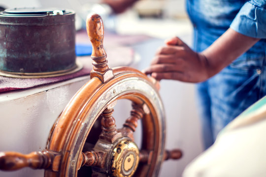 The hands of the captain and a steering wheel boat port services. Sea and travel concept