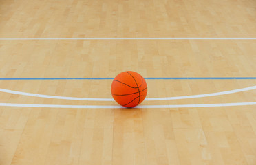 Basketball on a hardwood court floor as a sports and fitness symbol of a team leisure activity playing with a leather ball dribbling and passing in competition tournaments.