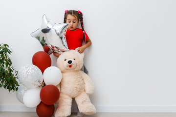 Happy brightful image of cute joyful little girl with balloons isolated on background. Amazing charming birthday fashionable kid looking to camera