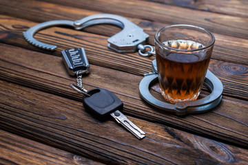 alcohol, handcuffs, car keys on wooden table background. driving under the influence. detention of the offender.
