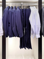 Man elegance classic formal cloth on wooden hangers. Design variety mens fashion jackets, trouses and shirts. Menswear sale. Man wardrobe for official dress code. Casual ironed clothes on metal rack