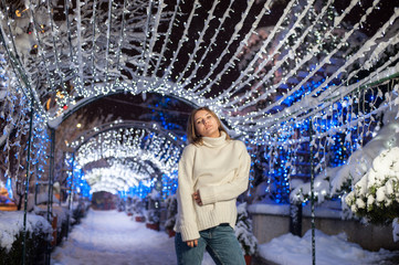 Pretty girl wearing blue jeans and a white top with snowflakes Christmas lights outdoor at night time.