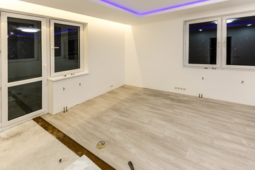 Installing light laminate floor with substrate under a laminate on white background