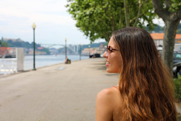 Happy smiling girl in Porto City, Portugal. Beautiful young tourist woman traveling in Europe.