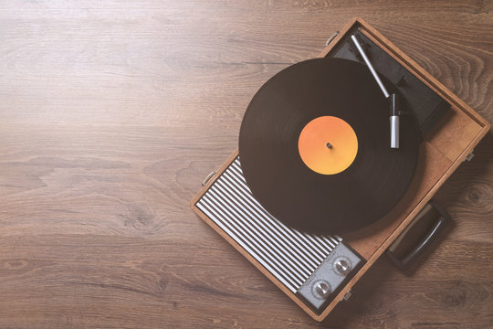 Older Gramophone with a vinyl record on wooden table, top view and copy space,photo.