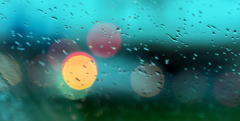 abstract pattern of colorful lights and rain drops during downpour on winshield of car