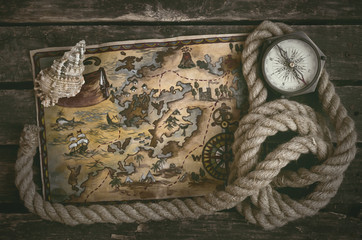 Pirate treasure map, compass, rope and seashell on a wooden table background.