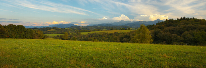 Panoramic view of Pyrenees with a green meadow on foreground at a sunset time