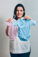 Pregnant woman showing baby bodysuits indoor. Selective focus on blue bodysuit in foreground