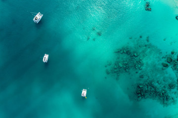 Spectacular aerial view of some yachts and small boats floating on a clear and turquoise sea, Seychelles in the Indian Ocean.Top view from drone