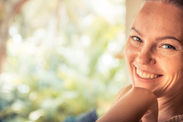 Young beautiful happy smiling tanned woman looking at camera portrait sunny day with copy space during tropical summer holidays