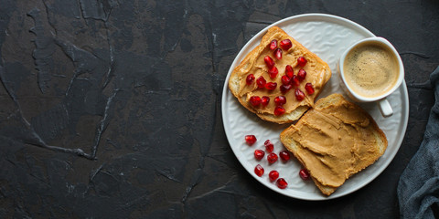 Sandwich with peanut paste and pomegranate grain red - breakfast or sweet snack (dessert). Top view. copy space