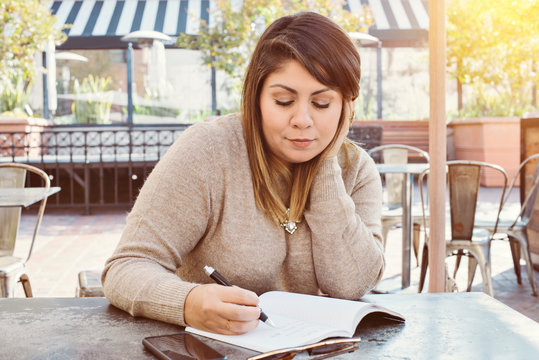 Latina girl ponders while writing in her journal in an outdoor café