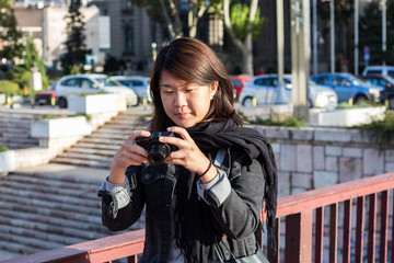 Chinese Girl Standing on the Bridge and Checking Picture She Took With Her Photo Camera