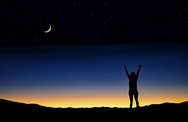 Person with raised arms silhouetted against the sunset and crescent moon.