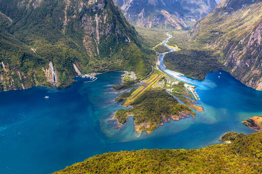 New Zealand. Milford Sound (Piopiotahi) from above - the head of the fiord with wharf and Milford Sound Airport. There is Cleddau River in the background