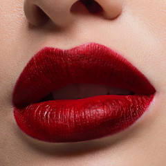 Macro photo of plump lips with bright matte lipstick. Clean skin, lip injections. Evening fashion makeup closed mouth