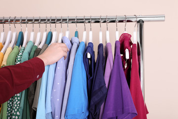 Woman choosing clothes from wardrobe rack on color background, closeup