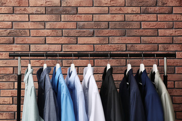 Wardrobe rack with stylish clothes near brick wall