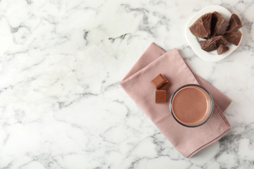 Flat lay composition with glass of tasty chocolate milk and space for text on marble background. Dairy drink