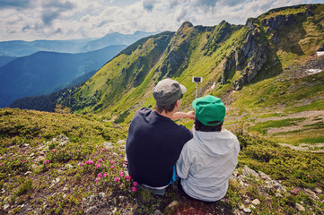 Young couple hiking taking selfie with smart phone.