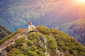 Young girl doing yoga or fitness exercise outdoor in nature with beautiful sky landscape, Namaste pose.