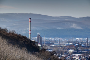 Winter cityscape with tall chimneys and industrial buildings in Diosgyor Vasgyar district of Miskolc with forested Bukk Mountains of North Hungarian Mountain Range, Hungary Eastern / Central Europe
