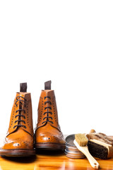 Mens Brogues Boots In Line With Cleaning Accessories on Shiny Table.Against White Background.