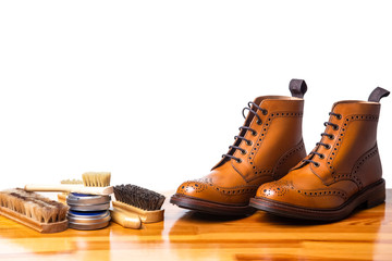 Mens Brogues Boots In Line With Cleaning Accessories on Shiny Table.Against White.