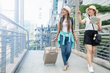 two Asian female tourist travelers in city with luggage and map