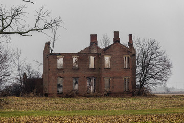 Old abandoned vintage mansion in middle of farm field with barren trees