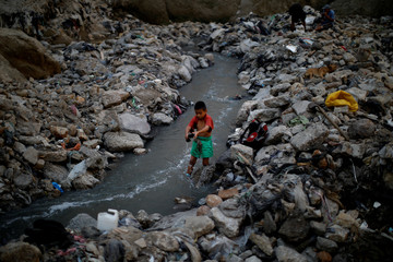Mauricio, a ten-year-old boy, washes clothes in contaminated sewage water at an area known as 'the Mine', where informal workers search for scrap metal, in the largest garbage dump of Guatemala City