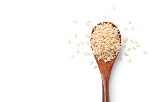 Brown rice in a wooden spoon isolated on white background