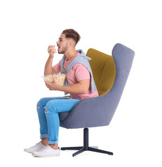 Handsome young man with bowl of popcorn in armchair on white background. Watching cinema