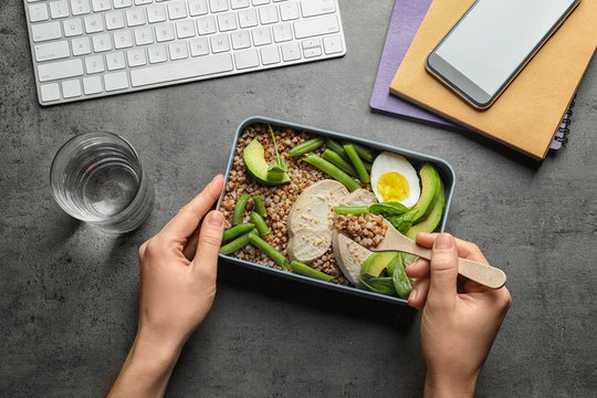 Woman eating natural protein food from container at office table, top view