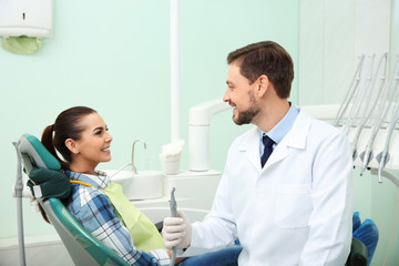 Professional dentist and happy patient in modern clinic