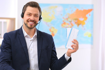 Male consultant with headset holding tickets in travel agency