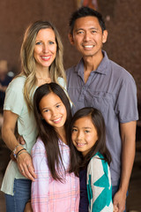 Portrait of a mixed race family with two children.
