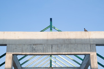 A bird on structure of concrete for building construction on blue sky background. Minimal